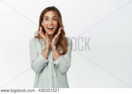 Surprised And Happy Middle Aged Woman Gasping Flattered, Holding Hands Near Face Ad Smiling Fascinat
