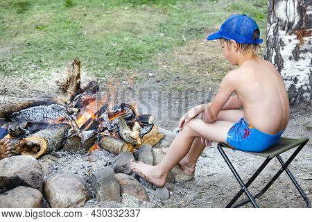Boy In Swimming Trunks And Cap Is Warming Himself By Fire In Forest After Swimming. Campfire In Camp