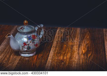 A Teapot On The Background Of An Ancient Torn Texture. Action. Beautiful Shiny Teapot For Tea Infuse