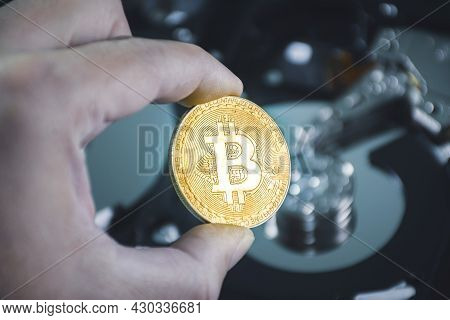 Close Up Of Gold Bitcoin In The Hand With Hard Disk Platters Blurred On Background