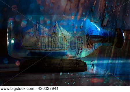 The Ship In Bottle In Thunderstorm With The Blurred Raindrops. Representing The Thoughts Of Isolatio