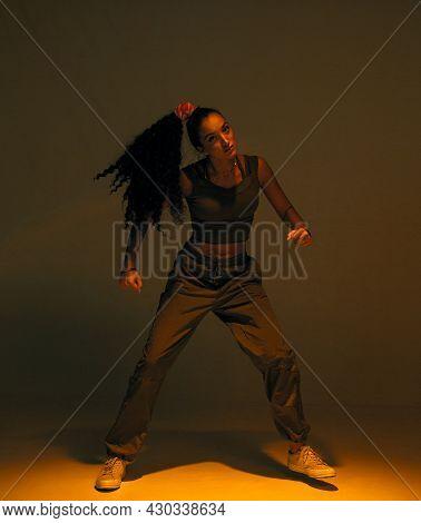 Dancing Mixed Race Girl In Warm Studio Light. Female Dancer Performing Expressive Ethnic Hip Hop Dan