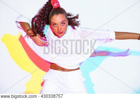 Dancing Mixed Race Young Girl In Colourful Rainbow Studio Light. Female Dancer With Afro Hairs On Wh
