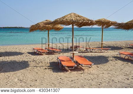 Sunshades On The Tropical Sandy Beach Against Turquoise Sea Water.