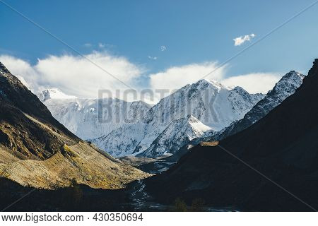 Atmospheric Landscape With High Snowy Mountain With Peaked Top Under Cirrus Clouds In Sky. Low Cloud