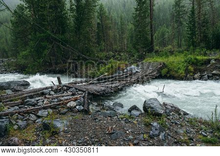 Atmospheric Rainy Landscape With Forest And Bridge Over Mountain River. Dark Forest Scenery With Pow