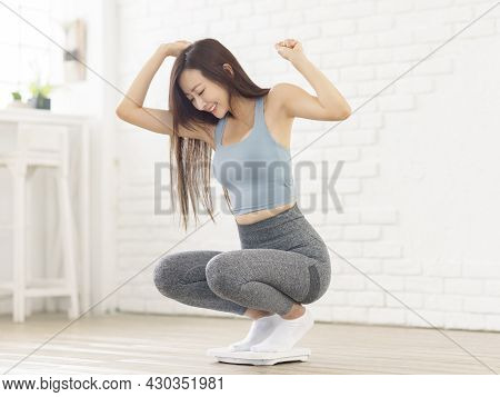 Excited Woman Sitting On Scales At Home, Overjoyed With Success Of Weight Loss.