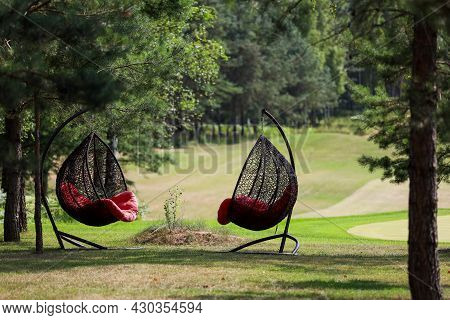 Hanging Chair With A Red Plaid On A Golf Course.