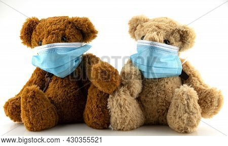 Two Teddy Bears Wearing Protective Mask, Teddy Bear Are Sitting In Blue Medical Masks On White Backg