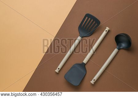 Three Kitchen Utensils On A Two-tone Brown Background. Plastic Kitchen Tools. Flat Lay.