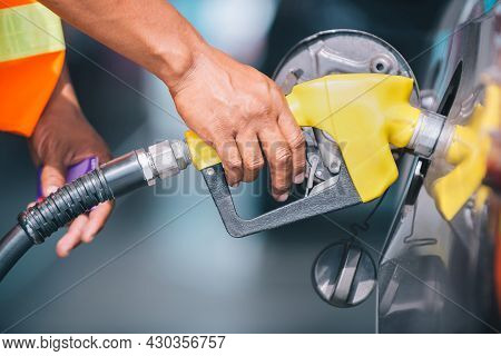 Car Refueling On The Petrol Station. Male Employees Controlled The Fuel Pump With Fuel Nozzles Addin