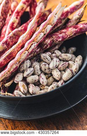 Cranberry beans. Borlotti beans in bowl. Beans pods