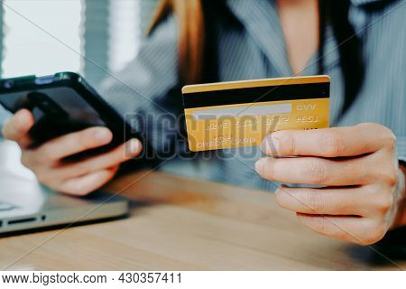 Asian Woman Holding Credit Card And Using Mobile Phone To Pay For Online Shopping. The Concept Of Pa