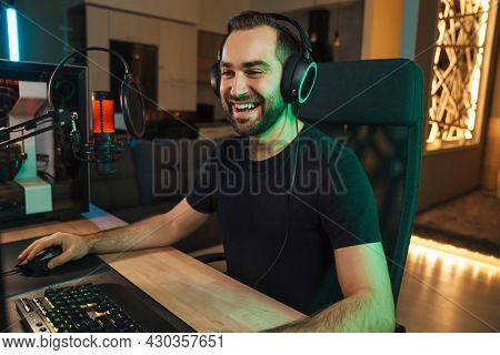 Happy young man gamer streamer in headphones playing on computer talking with players on chat in gaming competition