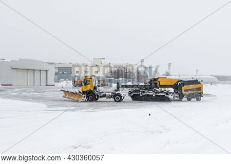 Airfield Snow Blowers Cleaning The Area Near The Airplane Hangar At The Airport In A Severe Blizzard