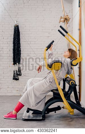 Portrait Of Lazy Middle Aged Woman Wearing Bathrobe And Sleeping On Exercise Simulator In Gym