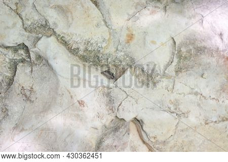Close Up And Soft Focus Of The Surface Of A Large Uneven Light Natural Cracked And Fractured Rock In