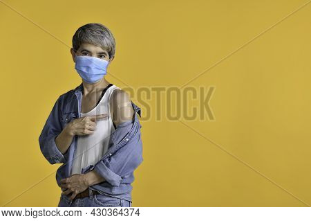 Happy Middle Aged Asian Woman Vaccinated Pointing Finger At Adhesive Plaster Bandage On Her Arm Afte