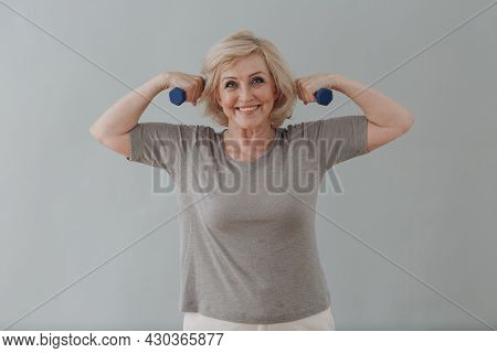 Elderly Caucasian Old Aged Woman Portrait Gray Haired Doing Exercises With Dumbbells Showing Biceps