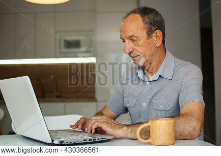 Trendy Mature Man Is Working From Home With Laptop Sitting At The Table In His Kitchen, Happy Retire