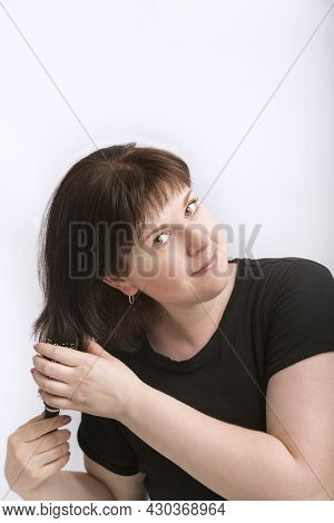 Portrait Of Young Woman With Natural Dark Hair Isolated On White Background. Girl Corrects Her Hair.