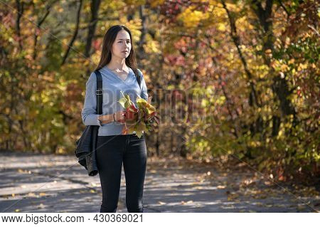 Sad Young Woman Is Walking Along The Alley Of The Autumn Park. Young Lonely Girl With Bouquet Leaves