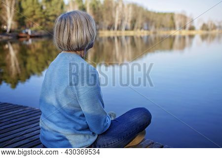 Senior Woman In Blue Pullover Sits On The Shore Of Lake, Have A Rest And Enjoys Calm And Nature, Men