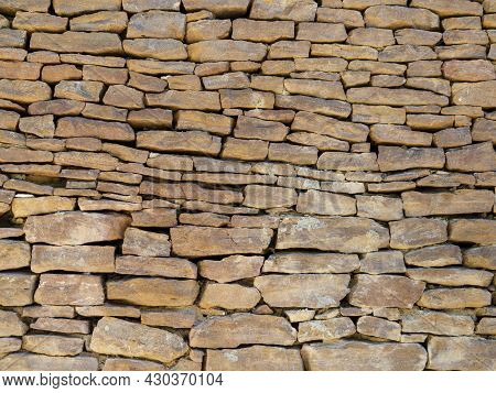 The Texture Of Ancient Historical Masonry Wall Made Of Different Sizes Of Stones Without The Use Of