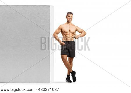 Full length portrait of a muscular guy leaning shirtless on a wall and showing his abs isolated on white background