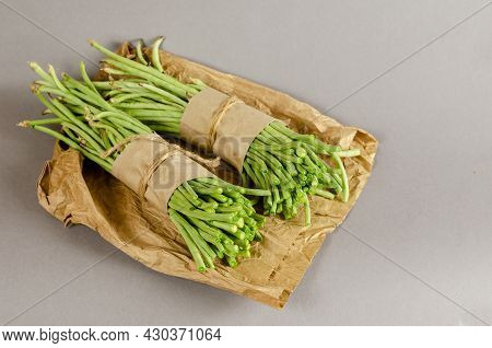 Bundles Of Raw Green Beans Against A Gray Background. Two Bundles Of Bean Asparagus Wrapped In Paper