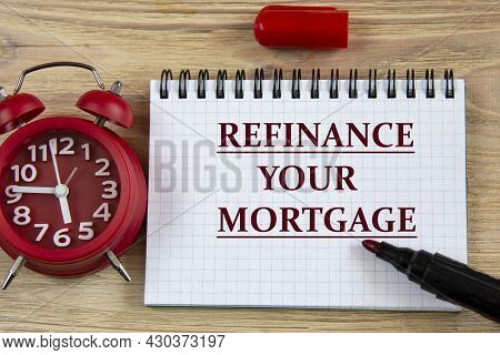 Refinance Your Mortgage - Words In A Notebook On A Wooden Background With An Alarm Clock And A Marke