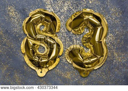 The Number Of The Balloon Made Of Golden Foil, The Number Eighty-three On A Gray Background With Seq