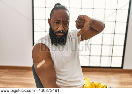 African american man getting vaccine showing arm with band aid with angry face, negative sign showing dislike with thumbs down, rejection concept
