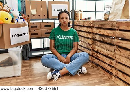 Young african american woman wearing volunteer t shirt at donations stand puffing cheeks with funny face. mouth inflated with air, crazy expression.