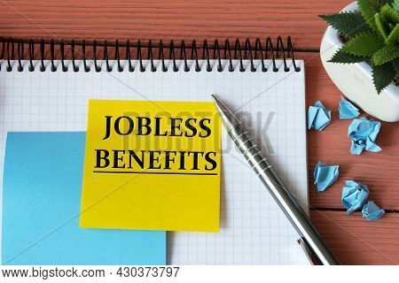 Jobless Benefits - Word On A Note Sheet With A Cactus In The Background. Info Concept