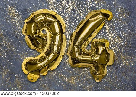 The Number Of The Balloon Made Of Golden Foil, The Number Ninety-four On A Gray Background With Sequ