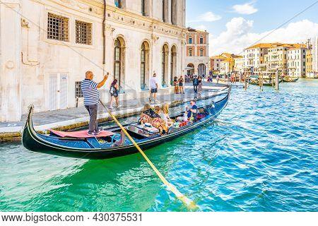 Venice, Italy - August 02, 2021: Tourists And Gondolier On Gondola Boat. Romantic Gondola Cruise In