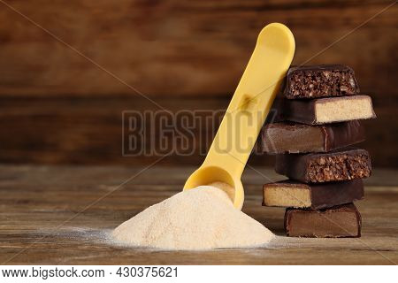 Pieces Of Tasty Bars And Scoop With Protein Powder On Wooden Table. Space For Text