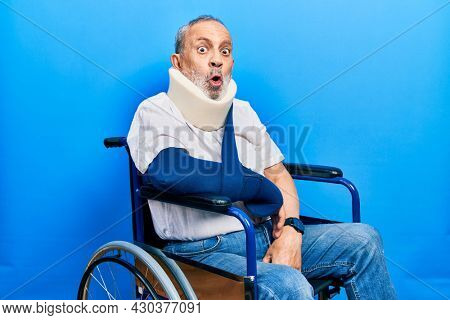 Handsome senior man with beard sitting on wheelchair with neck collar an arm sling scared and amazed with open mouth for surprise, disbelief face