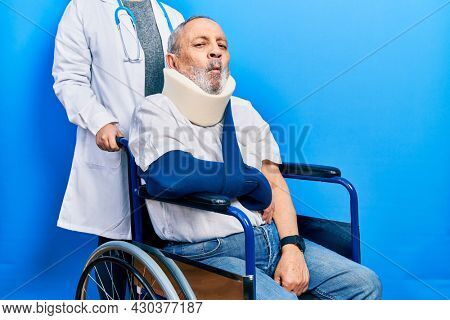 Handsome senior man with beard sitting on wheelchair with neck collar making fish face with lips, crazy and comical gesture. funny expression.