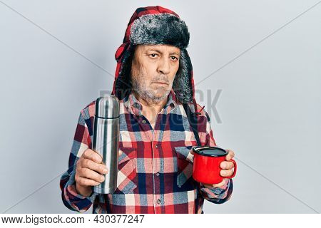 Handsome mature handyman wearing winter hat with ear flaps drinking hot coffee from thermo relaxed with serious expression on face. simple and natural looking at the camera.