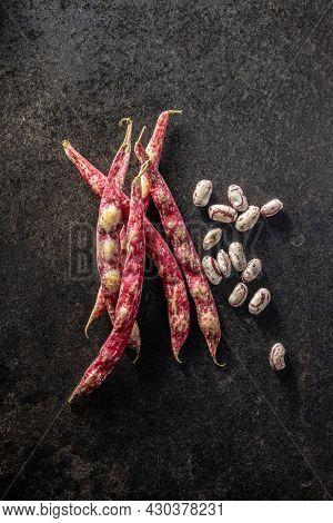 Cranberry beans. Borlotti beans. Beans pods on black table. Top view.