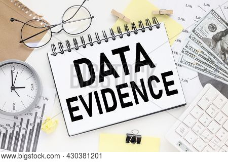Data Evidence, On A White Table On The Background Of Financial Charts And Glasses Notepad With Text
