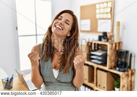 Middle age hispanic woman at the office very happy and excited doing winner gesture with arms raised, smiling and screaming for success. celebration concept.
