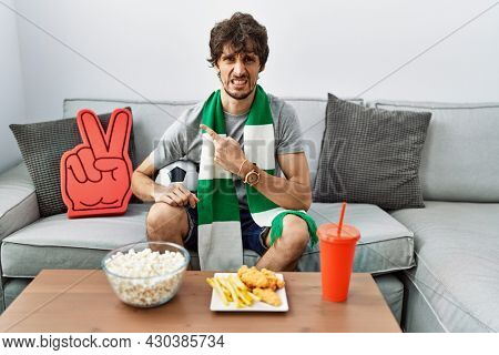 Young hispanic man football hooligan cheering game at home pointing aside worried and nervous with forefinger, concerned and surprised expression
