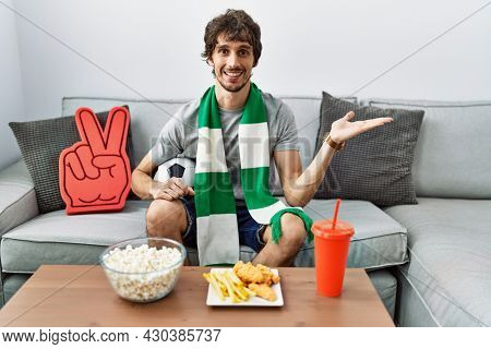 Young hispanic man football hooligan cheering game at home smiling cheerful presenting and pointing with palm of hand looking at the camera.
