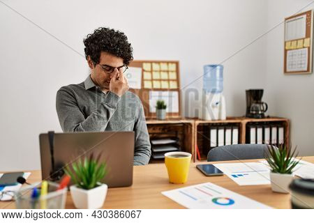 Young hispanic man wearing business style sitting on desk at office tired rubbing nose and eyes feeling fatigue and headache. stress and frustration concept.