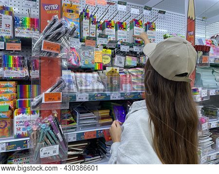 The Girl Takes A Box With Colored Pencils From The Showcase. Buying A Stationery For The School. Rus