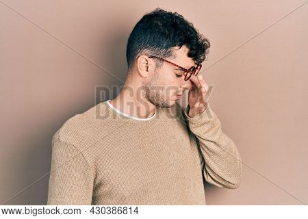 Young hispanic man wearing casual clothes and glasses tired rubbing nose and eyes feeling fatigue and headache. stress and frustration concept.