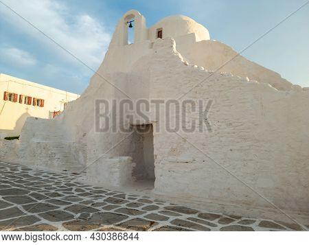 Panagia Paraportiani Greek Orthodox Christian traditional church as religious destination at Mykonos island, Cyclades, Greece. Whitewashed stonewall chapel cobblestone yard at Chora summer sunny day.
